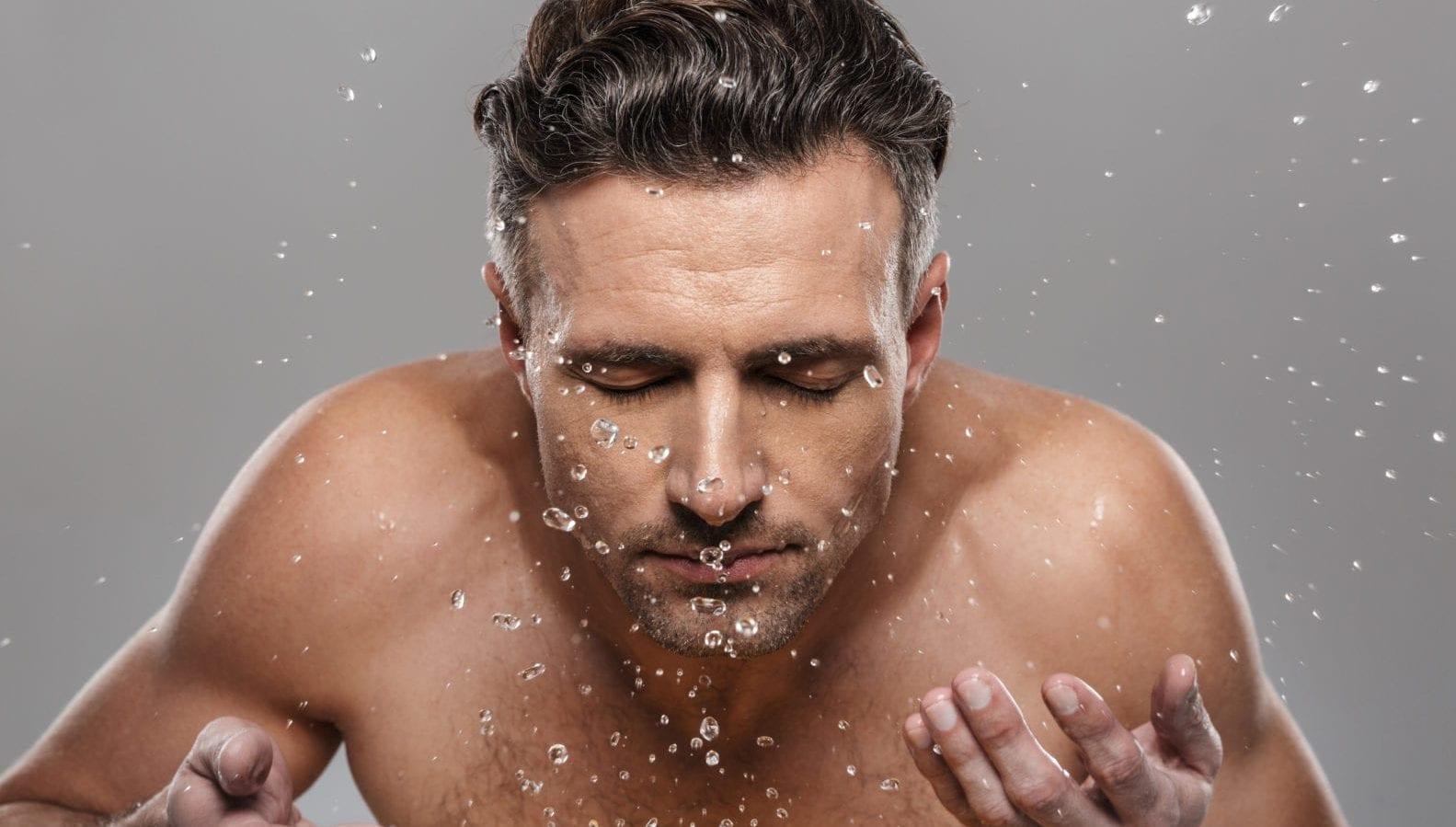 Reinig je huid elke ochtend en avond | man spat water in zijn gezicht | gezicht reinigen