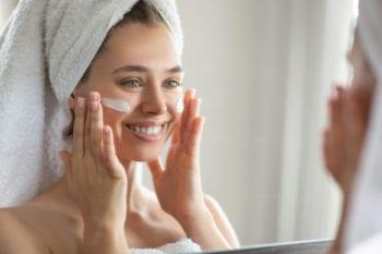 vrouw brengt creme aan op gezicht | huidverzorging