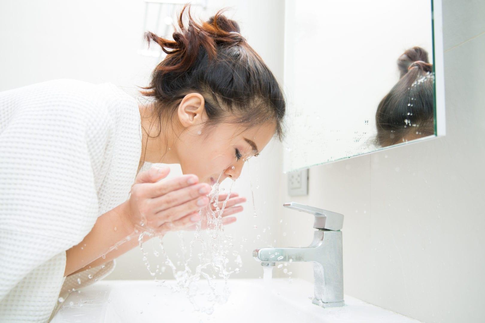 Vrouw wast haar gezicht in de badkamer